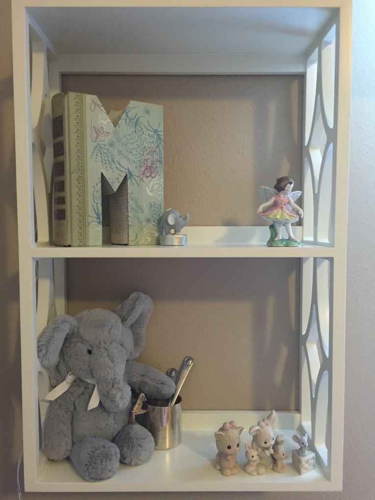 "The shelves are decorated with sentimental trinkets. The ""M"" is made out of a book and is a souvenir I bought when Troy and I went on our ""babymoon"" to St. Augustine in October. The fairy is a gift that my mom bought for my maternal grandmother years ago. My grandma gave it to me a couple years ago. The stuffed elephant is holding onto a silver cup that holds some of Troy's baby spoons. And the Precious Moments figurines are mine from when I was a child."