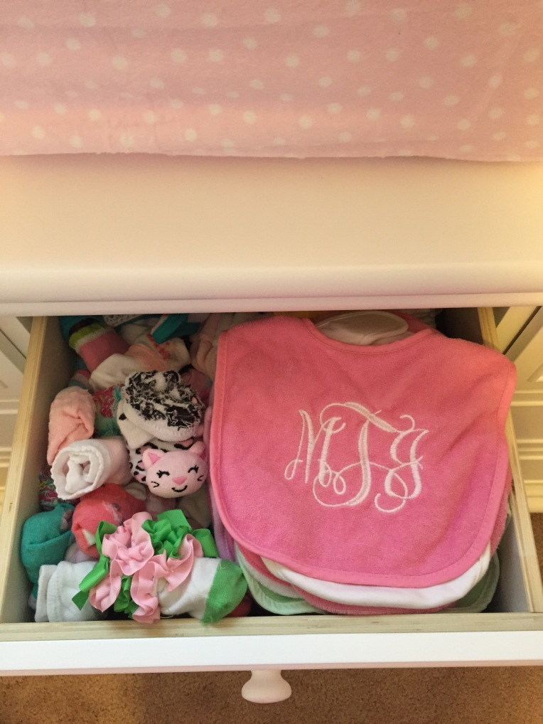 A dresser drawer filled with cute socks and bibs.
