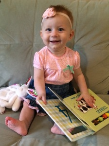 "Madelyn ""reading"" at seven months. She's in a book destruction phase, where she eats and tears the pages out of books, so we've learned that board books like the one in this picture are best at this age!"